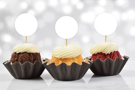 A tempting cupcake topper mockup featuring three delicious gourmet cupcakes on a white marble background. Add your own design to the cupcake toppers. Standard-Bild