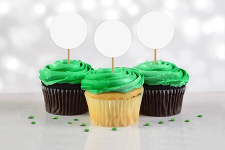 Three green frosted delicious cupcakes rest atop a white marble background surrounded by green sprinkles. Great St. Patrick's Day or sports team cupcake mock up.