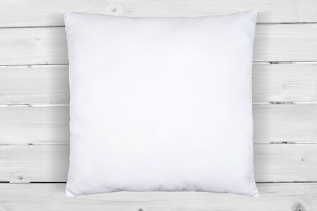 A white throw pillow makes itself comfortable atop a white wood plank background. This mock up features plenty of copy space so you can add your own design to the throw pillow. Stock fotó