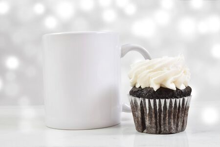 A white 11 ounce coffee cup chills gracefully next to a tempting chocolate cupcake with white frosting. A white light effect glows luxuriously in the background. Stock Photo
