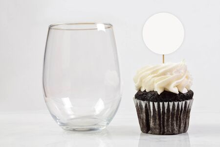 This cupcake topper and no stem wine glass mock up features an elegant stemless wineglass resting next to a tempting chocolate cupcake. 版權商用圖片