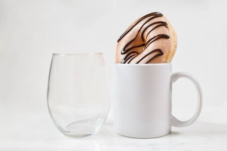 No stem wine glass chilling next to an 11 oz. white coffee mug. Coffee cup holds a tempting donut.