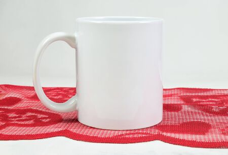 11 ounce white coffee cup resting romantically on a detailed red Valentine's Day table runner.