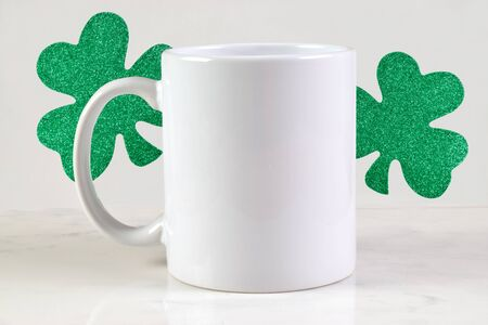 11 ounce white coffee cup sitting happily on a white marble background surrounded by glittery St. Patrick's Day shamrocks.