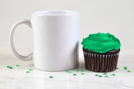 A green frosted chocolate cupcake rests temptingly next to an 11 ounce white coffee cup.