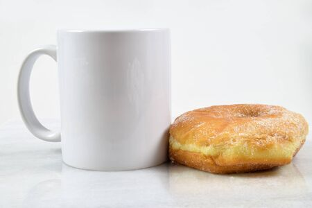 A delicious sugar coated donut sits temptingly next to an 11 oz. coffee cup.