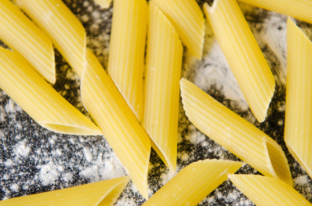 un used: pasta with flour on a dark table background