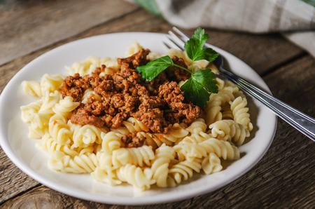 beef meat: hot pasta with sauce on a white plate on a wooden table