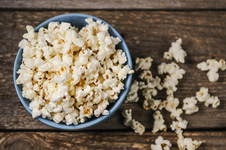 bowl of popcorn: Popcorn in a blue bowl on wooden table