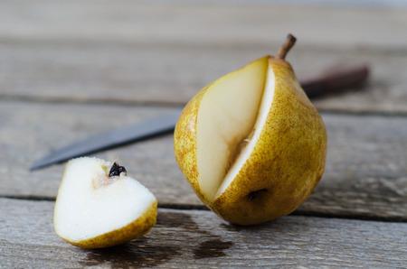 pera: rodajas peras maduras en una mesa de madera con cuchillo