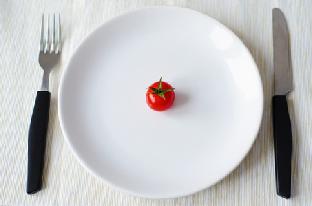 starvation: tomato served on a plate with fork and knife