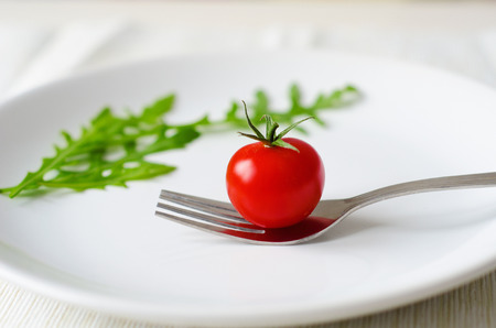 starvation: tomato served on white plate with fork and arugula