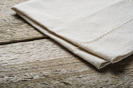 arnamentom: natural beige cotton cloth on wooden table Stock Photo