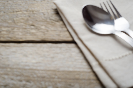 arnamentom: blurred background with a napkin and cutlery on wooden table