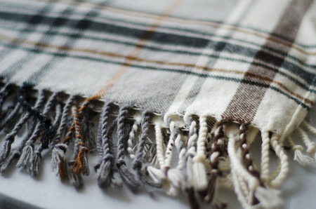 biege: grey and biege checkered knitted folded blanket  fringe