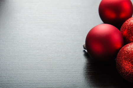 christmas deco: shiny red Christmas balls on a black wooden background