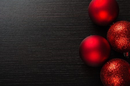 light red: shiny red Christmas balls on a black wooden background