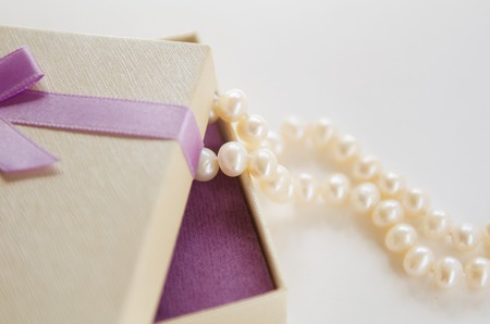 overhang: a necklace of pearls of the overhang of the gift box with a bow Stock Photo