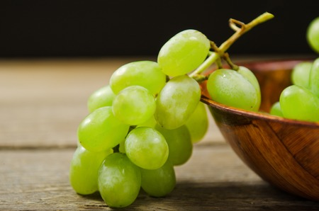 Green grapes. A branch of white grapes on grey wooden table. Black background.