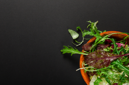 Green salad with rucola and lettuce in a bowl on black background. Top view, vegetarian, organic food.