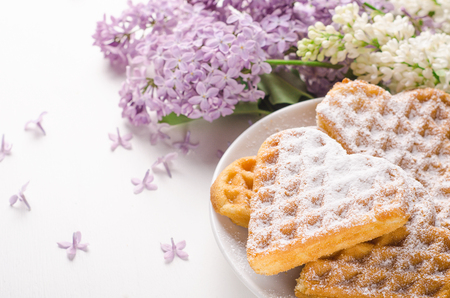 Homemade waffles heart sprinkled with powdered sugar on plate on a white table with flowers. Sweet pastry, breakfast.