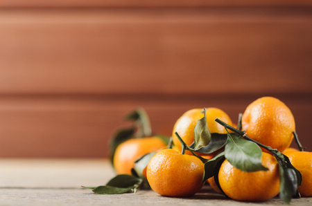 Fresh juicy little tangerines with green leaves in a heap on dark wooden background. Useful citrus fruit. Healthy food. Stock Photo