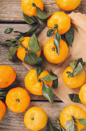 A pile of fresh sweet mandarins with green leaves on wooden table on craft paper. top view, flat lay