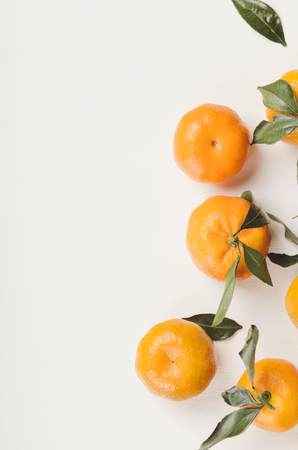 Orange sweet tangerines with green leaves on white background. Copy space, top view, flat lay