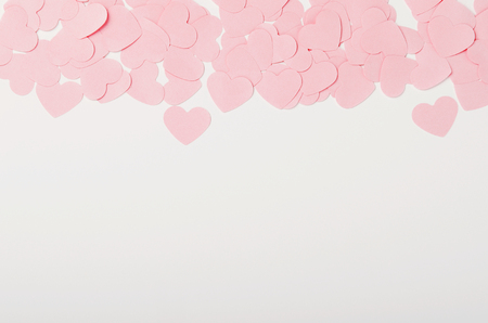 Small pink paper hearts on white background. Place for the inscription, congratulations on Valentines Day, March 8. Copy space, top view, flat lay Stock Photo