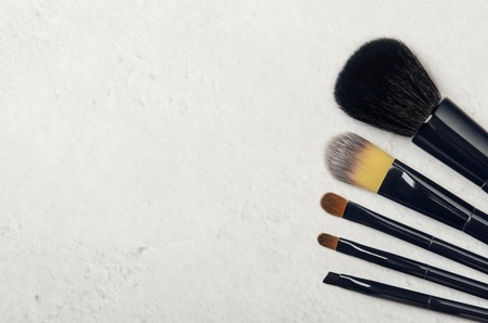 Black makeup brushes on a light stone background. Professional tools for make-up artist. Flat Lay, top view, copy space.
