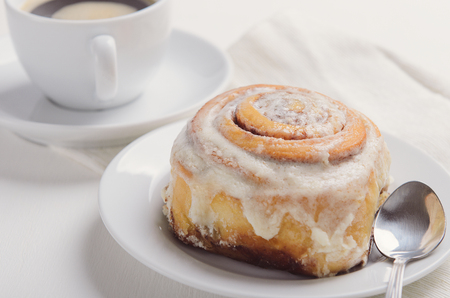 Hot cinnamon bun with sugar creamy icing on white plate. Sweet breakfast or snack with a cup of coffee.