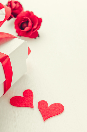White gift box with a red ribbon on white background with flowers and two hearts made of cloth. The concept of St. Valentine, womens day.