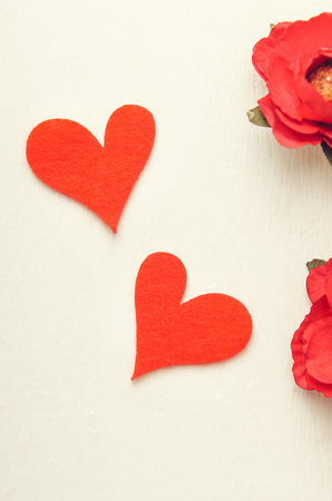Two red felt hearts on white background with red paper flowers. Valentines Day, love. Top view, flat lay. Stock Photo