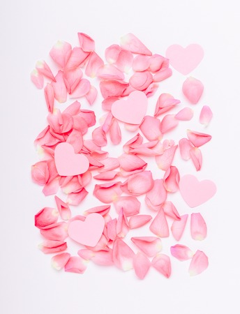 The composition of pink roses and hearts. Floral background for the holiday Womens Day, Valentines, Mothers Day. Copy space, top view, flat lay