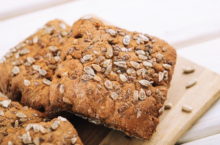 Bread with sunflower seeds on a white wooden background. Healthy food, rustic style. 免版税图像