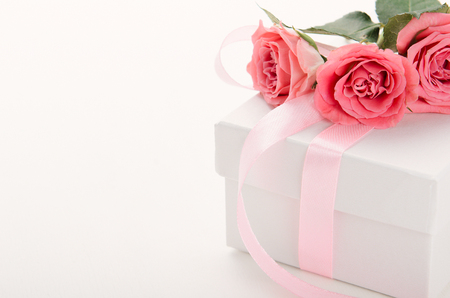 White gift box with pink ribbon and roses on white background. A gift for Valentines Day, birthday, womens day. Copy space. Stock Photo