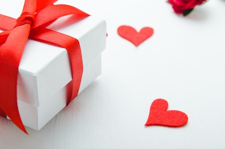 White gift box with a red bow on white background with hearts of felt. Concept congratulation on Valentines Day, Womens Day. Stock Photo