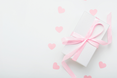 White gift box with pink ribbon and hearts on a white background. Valentines day gift, womens day. Copy space, top view, flat lay.