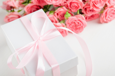 White gift box with a pink ribbon and a bouquet of roses on a white background. A gift for Valentines Day, birthday, womens day