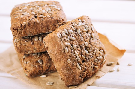 Bread with sunflower seeds on a white wooden background. Healthy food, rustic style. Stock fotó