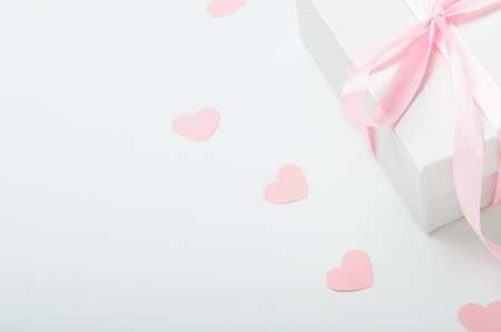 White gift box with pink ribbon and hearts on a white background. Valentines day gift, womens day. Copy space