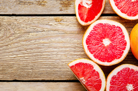 Sliced grapefruit and halves on wooden background. Useful citrus diet fruit. Copy space, top view, flat lay.