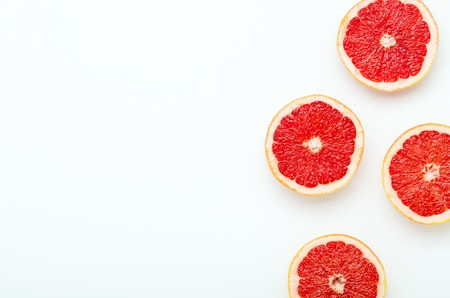 Grapefruit cut in halves on a white background. Copy space, top view, flat lay.