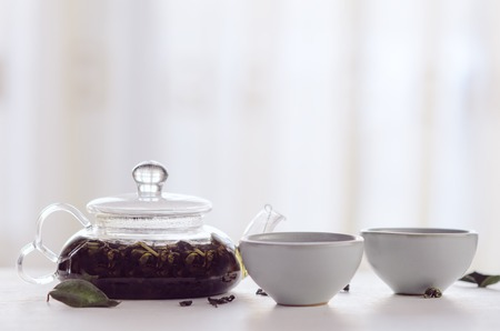 Black tea brewed in a transparent teapot with small cups on a white table. Concept tea ceremony, Chinese tradition, healthy drink Stock fotó