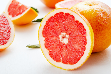 Grapefruits whole and halves on a white table. Fruit composition of useful citrus diet fruits
