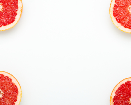 Frame of grapefruit halves on a white background. Minimal composition of healthy fruits. Copy space, top view, flat lay. Stock fotó