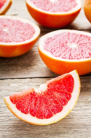 Sliced grapefruit and halves on wooden background. Useful citrus diet fruit
