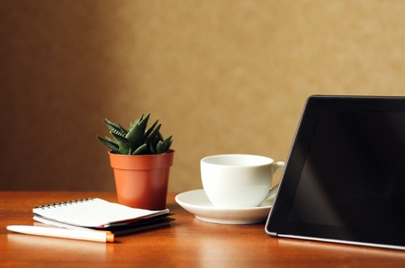 Desk at home office. Black tablet, indoor flower and notepad on a wooden table. Concept - work at home, freelancer