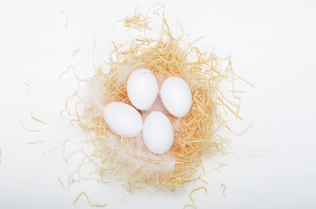 Eggs in a nest of hay on a white background. Concept easter composition, spring holiday, healthy food. Top view, flat lay. Stock fotó - 126192604