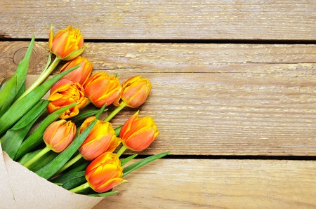 A bouquet of red-yellow tulips in kraft packaging on a wooden background. Copy space, top view, flat lay.